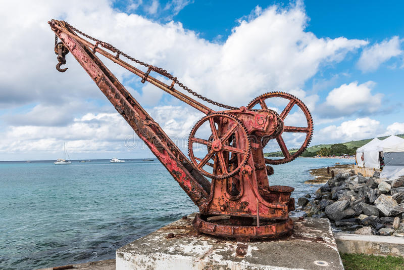 Antique red iron boat crane anchored in concrete along the shore royalty free stock images