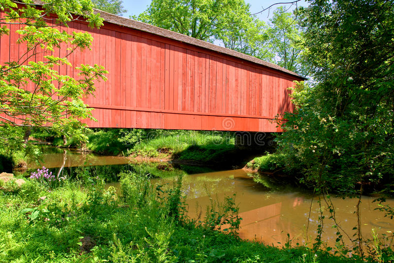 Antique Red Wood Covered Bridge over a River Creek royalty free stock images