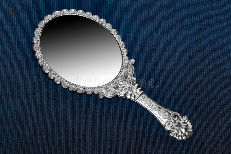 Antique retro hand mirror on dark blue background.  royalty free stock images