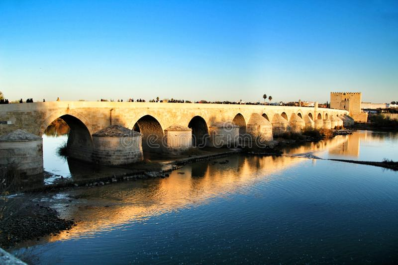 Antique roman bridge in Cordoba. Beautiful antique roman bridge over the Guadalquivir river at sunset in Cordoba , Spain stock image