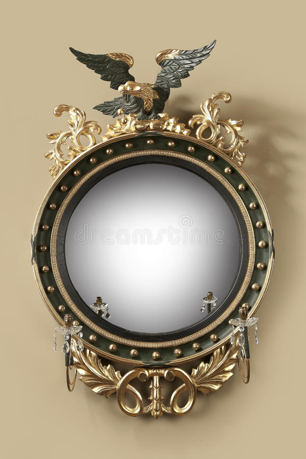 Antique round hall mirror. Old antique round convex guilded hall mirror with eagle and candle holders. 18 - 19th century royalty free stock images