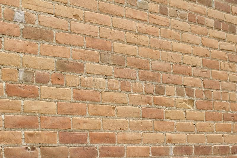 Antique sandy brown clay brick wall texture with a weathered and worn look royalty free stock photography