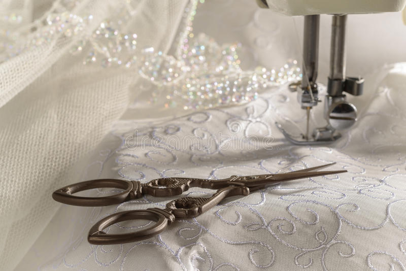 Antique Scissors. Against wedding dress material and sewing machine stock photo