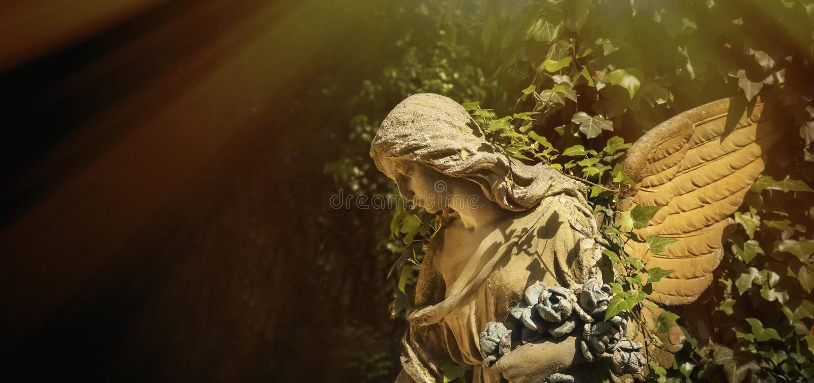 Antique sculpture of gold angel with wings against dark background.  stock photography