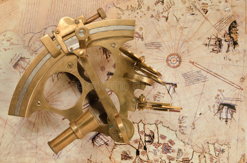 Antique sextant on old map royalty free stock images