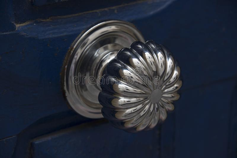 Antique silver doorknob - polished to a shine by years of use mounted on a blue door. Essaouria, Morocco - September 2017: Antique silver doorknob - polished to stock photo