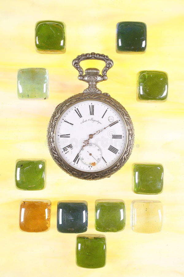 Antique silver pocket watch. Surrounded by cubes of colored glass stock photography
