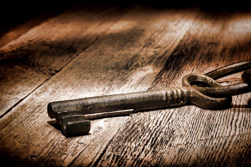 Antique Skeleton Key on Old Distressed Wood Planks. Antique medieval skeleton door lock key on old and weathered wood planks stock photos
