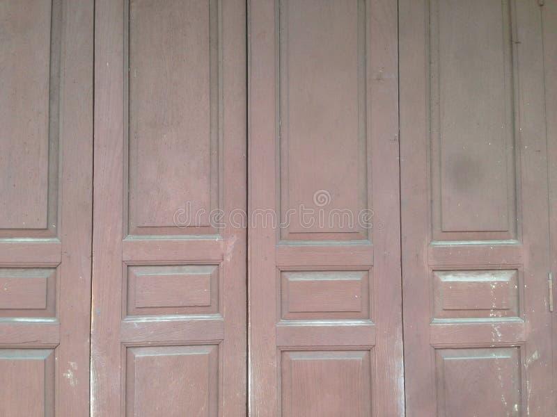 Antique sliding doors or folding doors at old wooden buildings. Wooden door hinges,Old wood door,Old brown wood door stock photography