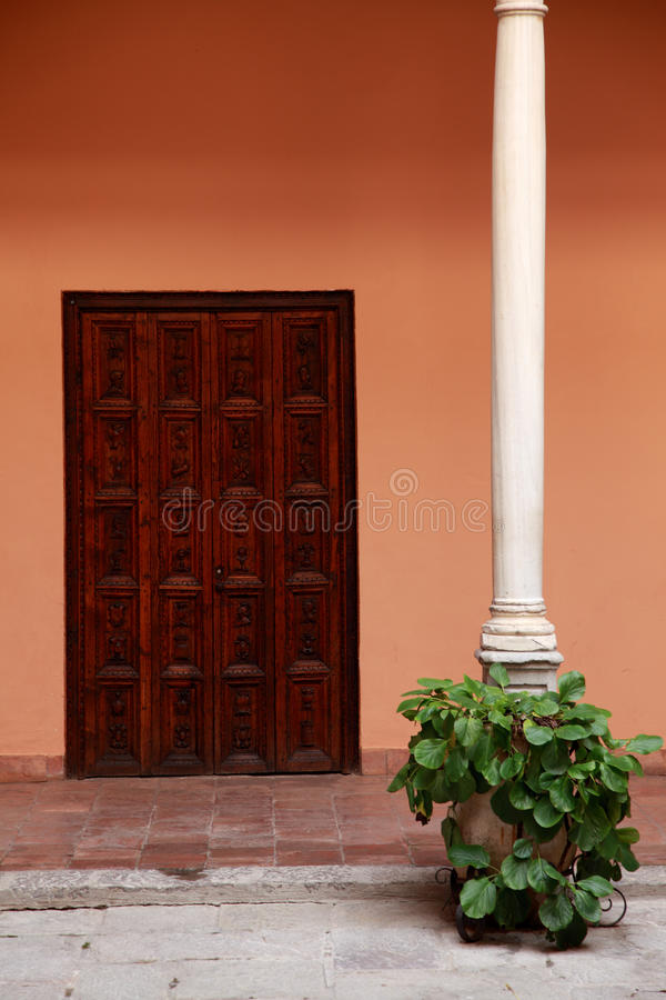 Antique Spanish door in old patio. Antique wooden door in a romantic patio wooden colon with plant in antique pot stock images