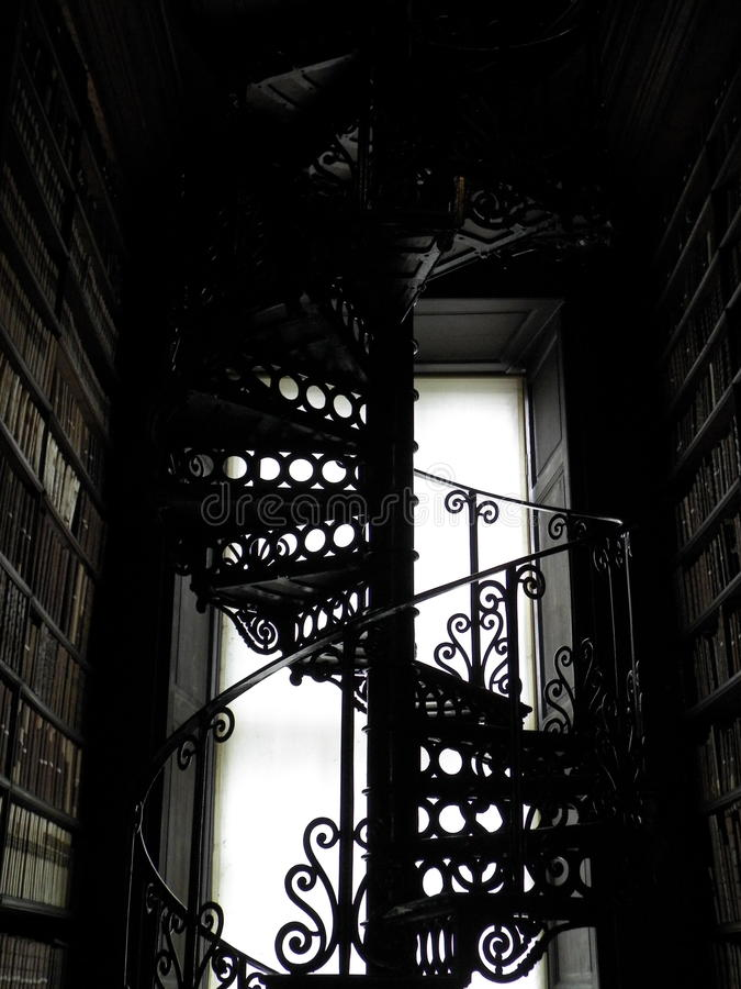 Antique Spiral Staircase. An antique metal spiral staircase at the library of Trinity College in Dublin silhouetted against a window royalty free stock images