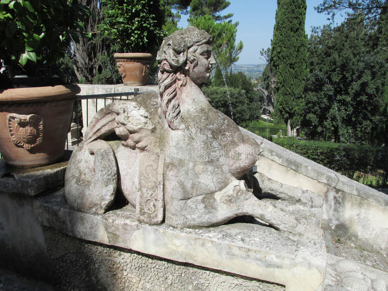 Antique statues Villa d'Este. Villa d'Este fountains and antique marble statues of gods, woman, mythological creatures and heraldic eagles. Beautiful green stock photography
