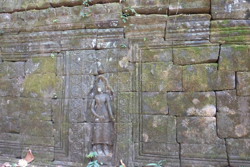 Antique stonework decorated with bas-relief. Stone carving. Ancient ruins overgrown with moss royalty free stock image