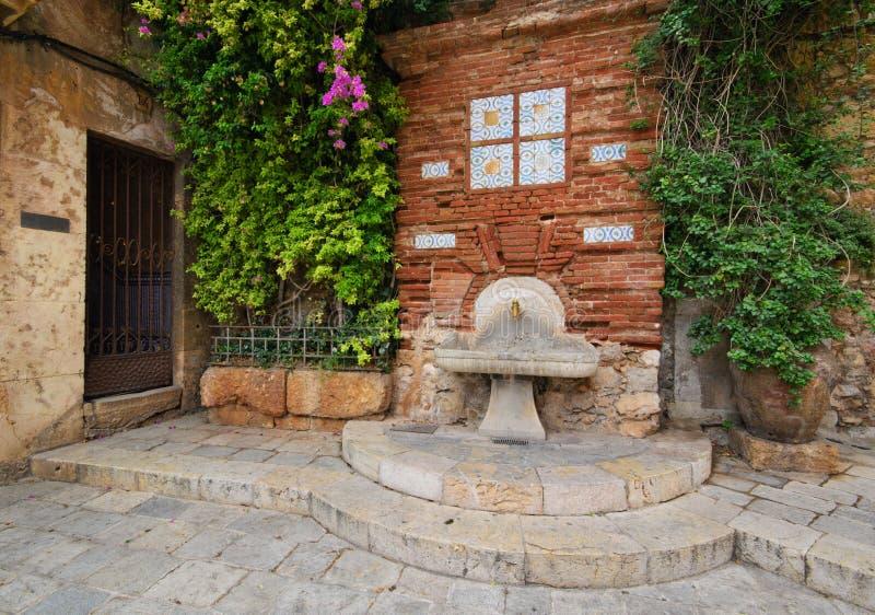 Antique street faucet. Antique column on the street drinking Tarragona, Spain royalty free stock photo