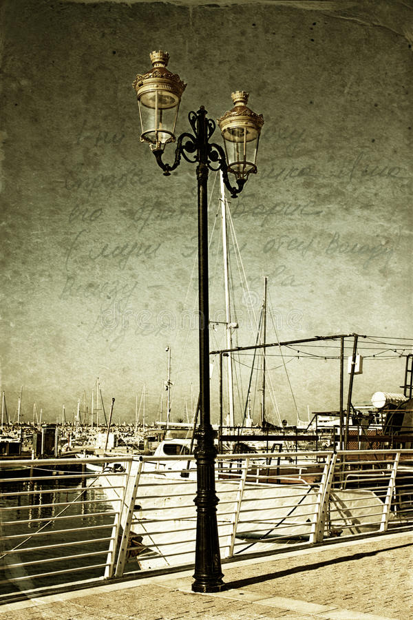 Antique street lamp with yacht and vintage style texture overlaid effect.  stock image