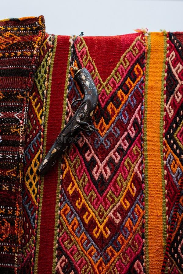 Antique stylistic revolve-like gun on traditional red rug. Antique stylistic revolve-like gun on a traditional red rug royalty free stock image