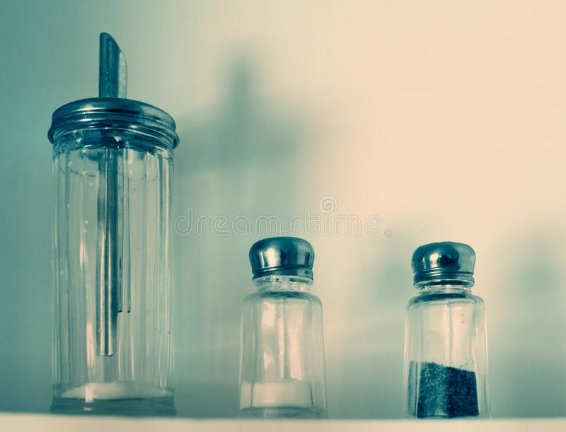Antique sugar, salt & pepper. Antique sugar, salt, and pepper shakers or containers on a shelf. Color modified for antique look royalty free stock photography