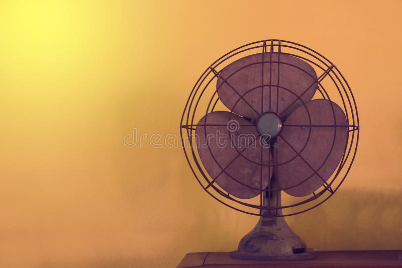 Antique table fan electric ventilator on wood table with vintage style effect. royalty free stock image