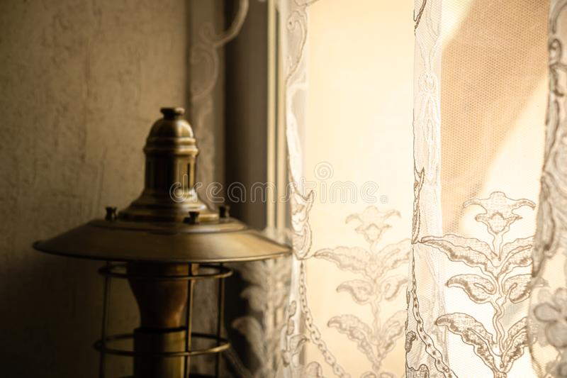Antique table lamp on the windowsill at the hotel. Before a sunny window with an openwork tulle royalty free stock photography