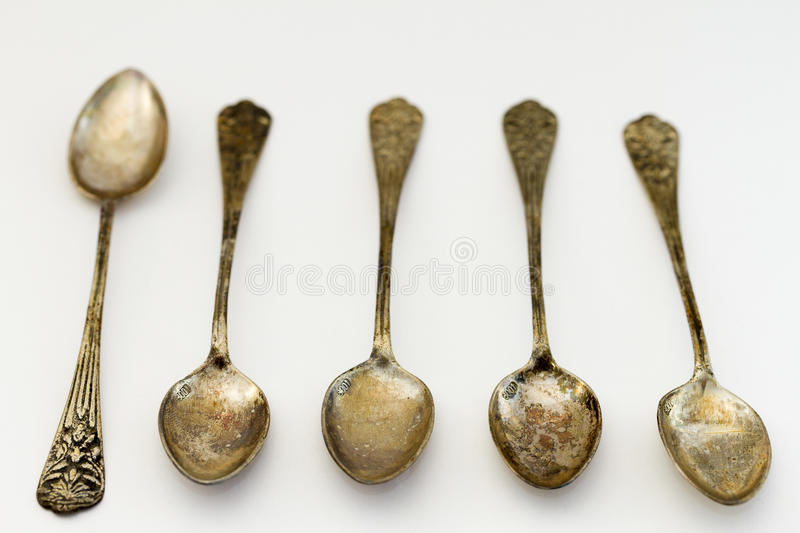 Antique tattered silver spoons. Collection of 5 antique silver spoons on neutral background royalty free stock image