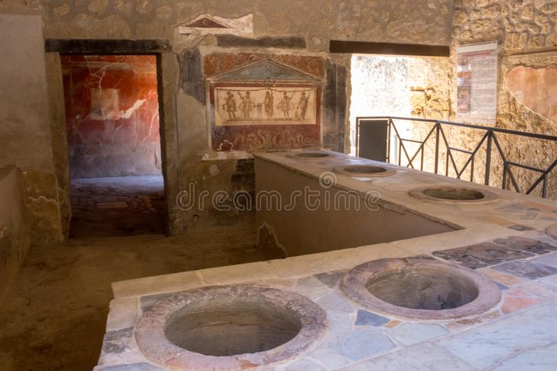 Antique tavern interior with fresco in Pompeii, Italy. Pompei ruins after volcano Vesuvius eruption. Historical heritage concept. royalty free stock images