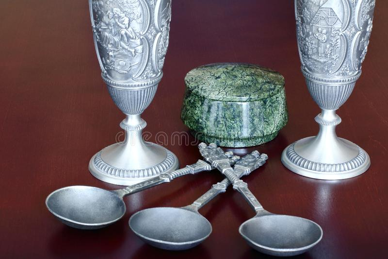 Antique tin cast wine glasses, antique metal soup spoons and a round box of green stone serpentine on a brown wooden background stock photography