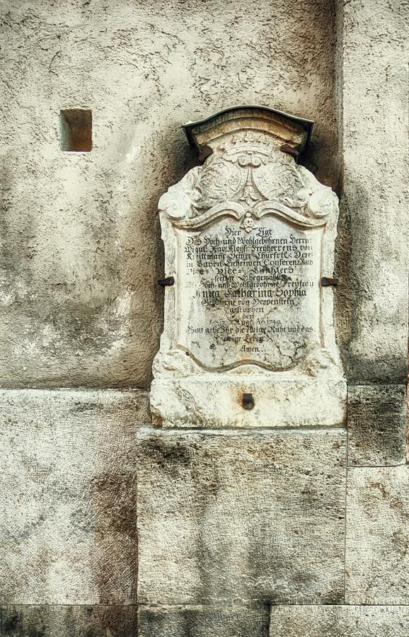 Antique tombstone with German inscription. Antique tombstone, year 1749, with carved inscription in old German, in a niche of a church wall royalty free stock photos
