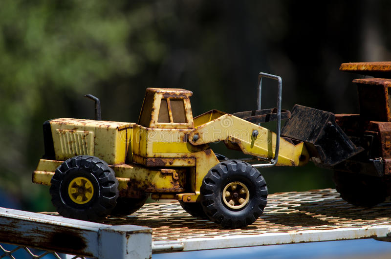 Antique toy front end loader. A slightly rusty toy front end loader looks like it is well loved and has been played with a lot stock photo