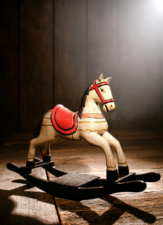 Antique Toy Rocking Horse in Old House Wood Attic. Antique reproduction rocking horse wood toy on aged wooden plank floor in a dusty old house attic in a royalty free stock images