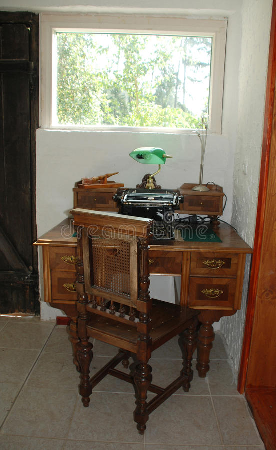 Antique Typewriter and Desk. An antique manual typewriter on a antique wooden desk stock photography