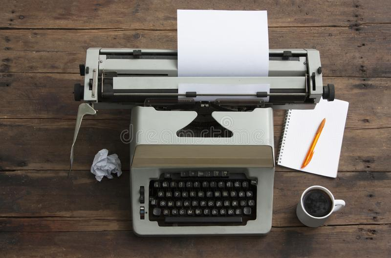 Antique typewriter with the Russian alphabet on a table, a notebook on a spring and a pen, a cup of coffee stock photos
