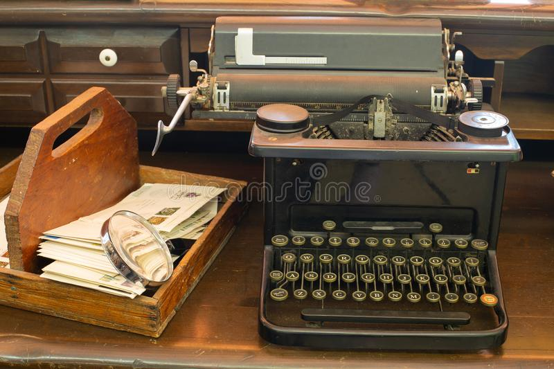 Antique typewriter sitting on a desktop with a letter box and an old magnifying glass stock photography