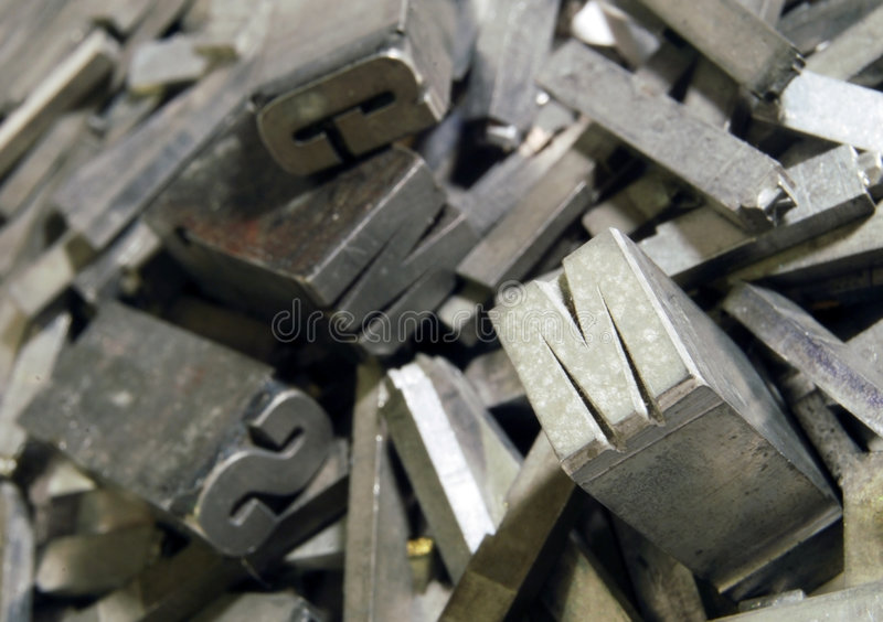 Antique typographic letters. A closeup view of a jumbled pile of antique lead typographic letters used in printing royalty free stock image
