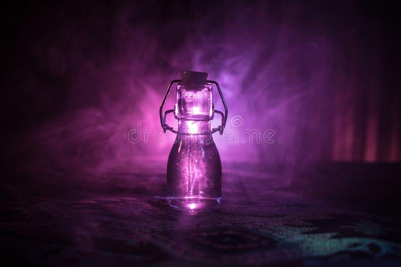Antique and vintage glass bottles on dark foggy background with light. Poison or magic liquid concept. royalty free stock photo