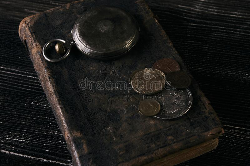 Antique vintage pocket watch and old leather book. With grunge coins on dark wooden table, close-up, top view. Time concept stock images
