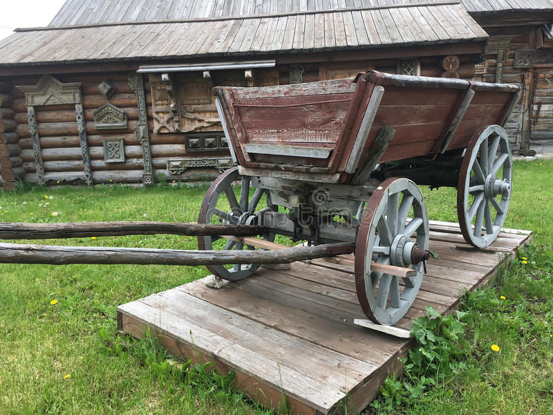 Antique vintage Russian rural peasant cart in the yard of a wooden house.  stock image