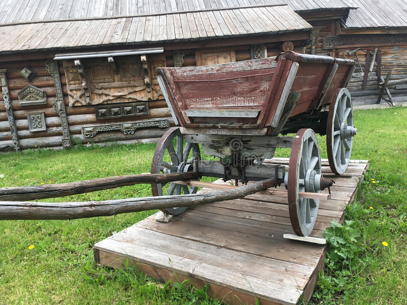 Antique vintage Russian rural peasant cart in the yard of a wooden house.  royalty free stock image