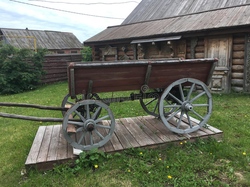 Antique vintage Russian rural peasant cart in the yard of a wooden house.  stock photos