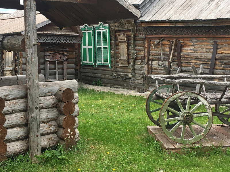 Antique vintage Russian rural peasant cart in the yard of a wooden house.  royalty free stock photos
