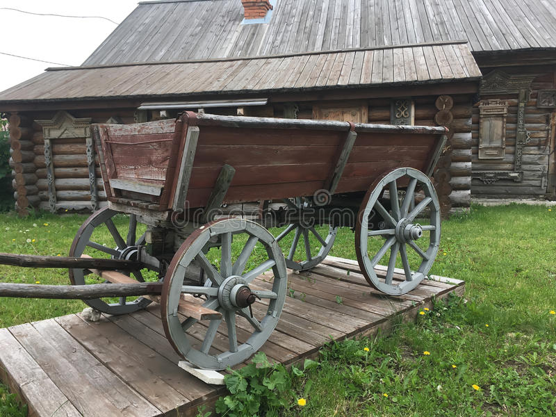 Antique vintage Russian rural peasant cart in the yard of a wooden house.  royalty free stock photography