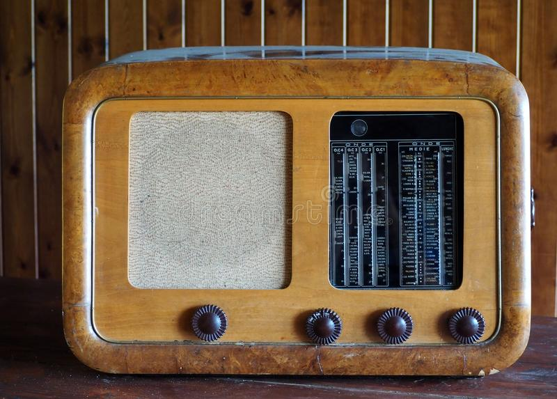 Antique vintage wooden radio on wood wall background. The black glass with the city names is written in italian . royalty free stock photo