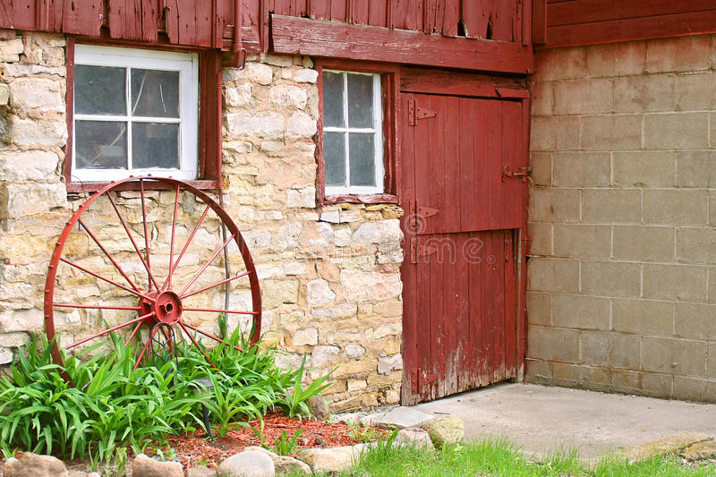Antique Wagon Wheel Leaning On Old Stone Barn Wall Stock