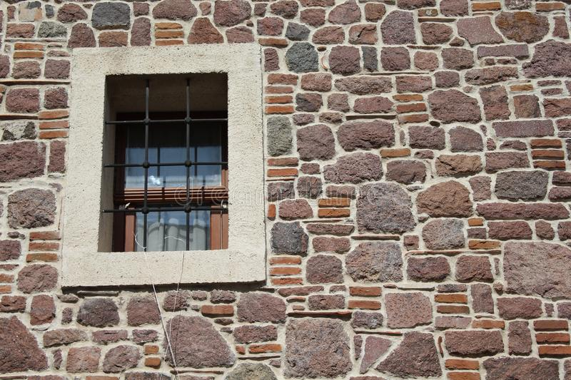 An antique wall and window. Antique wall window stones textuee texture abstract brown squarw square art ancient histort history background empty space copy stock photos