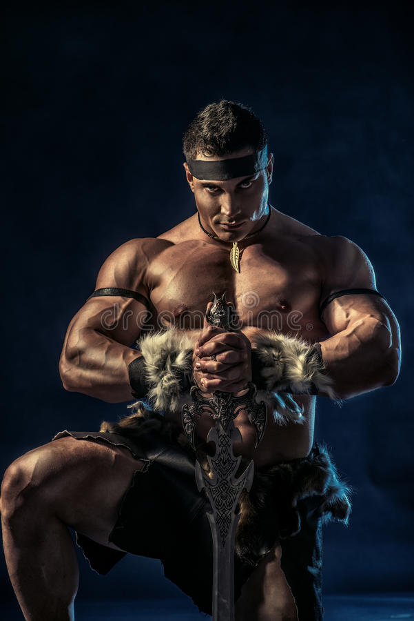 Antique warrior. Portrait of a handsome muscular ancient warrior with a sword stock photos