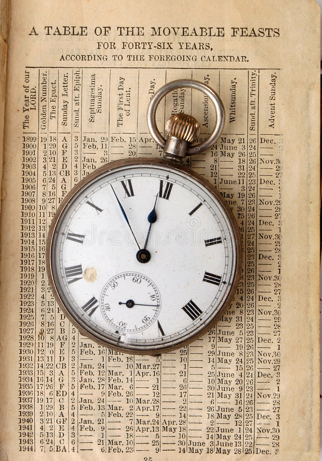 Antique watch on calendar. An antique pocket watch on an old religious calendar royalty free stock images