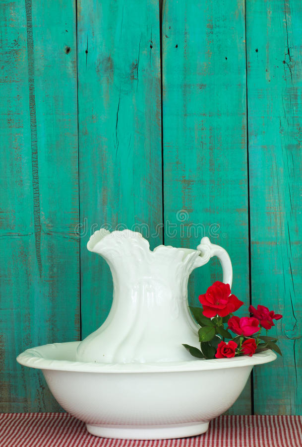Antique water pitcher and basin with red flowers by rustic green wood background. Antique white water pitcher and basin with red roses by old weathered teal blue stock photo