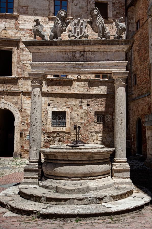 Ancient well Piazza Grande square, Montepulciano, Tuscany, Italy. Antique well decorated with griffins and lions holding symbol or coat of arms with balls, bolls royalty free stock photos