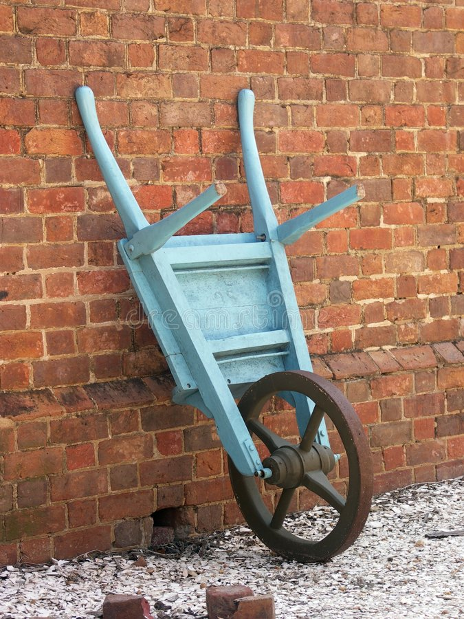 Antique Wheel Barrow Against Brick stock images