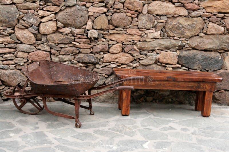 Antique wheelbarrow and bench stock photography