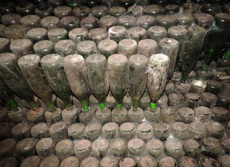 Antique wine bottles laying in wine cellar. Old wine in old winery. stock photos